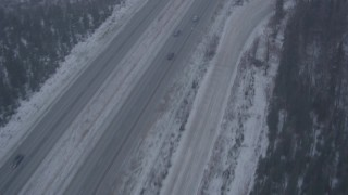 AK0001_1307 - 4K stock footage aerial video following Glenn Highway through forest and falling snow, Anchorage, Alaska