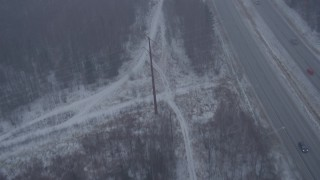AK0001_1308 - 4K stock footage aerial video following Glenn Highway and forest through snow, Anchorage, Alaska