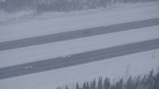 AK0001_1317 - 4K stock footage aerial video light traffic on Glenn Highway in falling snow, Anchorage, Alaska
