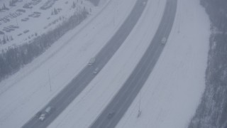 AK0001_1318 - 4K stock footage aerial video light traffic on Glenn Highway in falling snow, Anchorage, Alaska