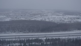 AK0001_1320 - 4K stock footage aerial video tracking cars on Glenn Highway in falling snow, Fort Richardson, Anchorage, Alaska