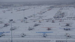 AK0001_1326 - 4K stock footage aerial video airplanes parked on snowy runway at Merrill Field, Anchorage, Alaska