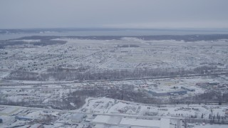 AK0001_1330 - 4K stock footage aerial video flying past snow covered Elmendorf Air Force Base, Anchorage, Alaska