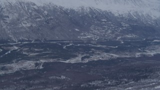 AK0001_1345 - 4K stock footage aerial video flying over snowy slope revealing a rocky range in the Chugach Mountains, Alaska