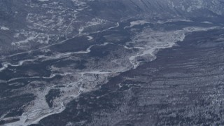 AK0001_1347 - 4K stock footage aerial video tilting up along Eagle River revealing snow covered Chugach Mountains, Alaska