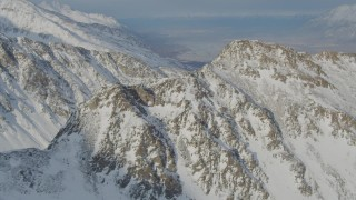 AK0001_1379 - 4K stock footage aerial video flying toward rocky, snow covered mountain summit, Chugach Mountains, Alaska
