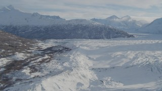 AK0001_1388 - 4K stock footage aerial video flying along edge of snow covered Knik Glacier toward Chugach Mountains, Alaska