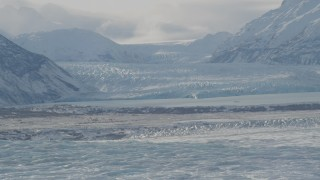 AK0001_1428 - 4K stock footage aerial video snow covered glacier spilling into Inner Lake George, from Knik Glacier, Alaska