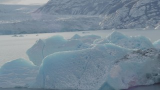AK0001_1433 - 4K stock footage aerial video orbiting a chunk of glacial ice in Inner Lake George, Alaska in snow
