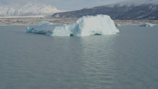 AK0001_1438 - 4K stock footage aerial video flying by a piece of glacial ice on Inner Lake George, Alaska in snow