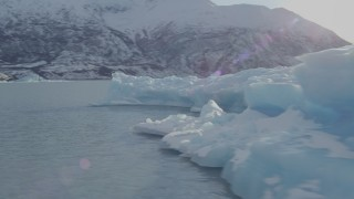 AK0001_1439 - 4K stock footage aerial video flying by a piece of glacial ice on Inner Lake George, Alaska in snow
