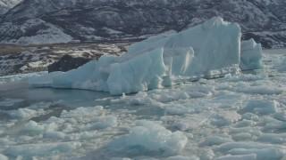 AK0001_1462 - 4K stock footage aerial video orbiting large chunks of glacial ice on Inner Lake George, Alaska in snow
