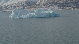 AK0001_1467 - 4K stock footage aerial video flying over Inner Lake George toward piece of glacial ice, Alaska in snow
