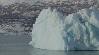 AK0001_1468 - 4K stock footage aerial video orbiting a piece of glacial ice on Inner Lake George, Alaska in snow