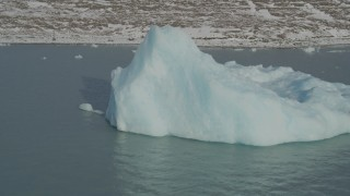 AK0001_1470 - 4K stock footage aerial video flying toward piece of glacial ice on Inner Lake George, Alaska in snow