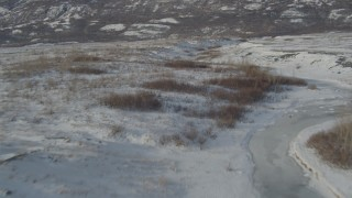 AK0001_1471 - 4K stock footage aerial video flying over snow covered ground and shallow creek, Inner Lake George, Alaska