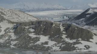 AK0001_1472 - 4K stock footage aerial video flying over snowy ridge toward the glacier on Inner Lake George, Alaska