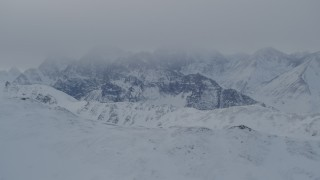 AK0001_1492 - 4K stock footage aerial video the snow covered Chugach Mountains capped by low clouds, Alaska