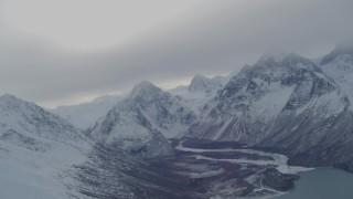 AK0001_1494 - 4K stock footage aerial video panning across snow covered Chugach Mountains revealing Eklutna Lake, Alaska