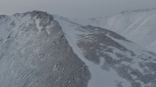 AK0001_1498 - 4K stock footage aerial video flying toward and over a snow covered slope in the Chugach Mountains, Alaska