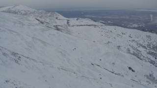 AK0001_1507 - 4K stock footage aerial video fly over snowy mountain slopes reveal Anchorage, Chugach Mountains, Alaska