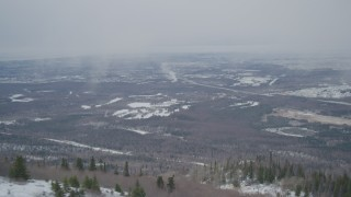 AK0001_1511 - 4K stock footage aerial video flying away from wooded slope revealing Anchorage, Alaska in snow