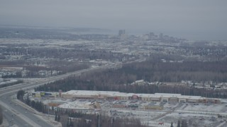 AK0001_1514 - 4K stock footage aerial video snow covered Downtown Anchorage, flying behind plume of steam, Alaska