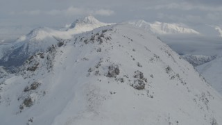 AK0001_1546 - 4K stock footage aerial video flying over snowy summit revealing snow capped Chugach Mountains, Alaska