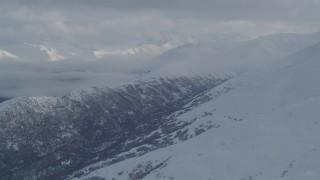 AK0001_1547 - 4K stock footage aerial video the snowy Chugach Mountains, cloud covered Eklutna Lake Valley, Alaska
