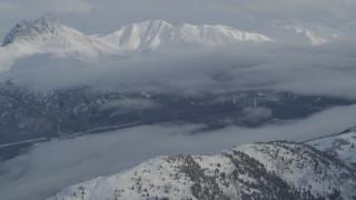 AK0001_1549 - 4K stock footage aerial video clouds covering Eklutna Lake Valley, snowy Chugach Mountains, Alaska