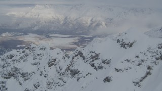 AK0001_1567 - 4K stock footage aerial video flying over snowy mountain ridges toward Butte, Chugach Mountains, Alaska