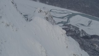 AK0001_1571 - 4K stock footage aerial video rounding snowy peak revealing Knik River Valley, Chugach Mountains, Alaska