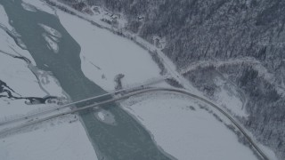 AK0001_1572 - 4K stock footage aerial video a reverse view of the Old Glenn Highway bridges spanning Knik River, Alaska in snow