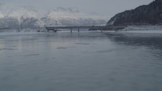 AK0001_1573 - 4K stock footage aerial video flying over Knik River toward Old Glenn Highway bridges, Alaska in snow