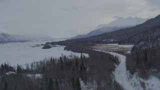 AK0001_1579 - 4K stock footage aerial video flying over Knik River Road in snow covered Knik River Valley, Alaska