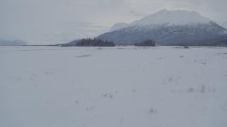 AK0001_1589 - 4K stock footage aerial video fly over snowy ground toward Chugach Mountains, Knik River Valley, Alaska