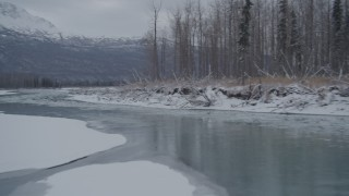 AK0001_1602 - 4K stock footage aerial video following an icy river between snowy shore, Knik River Valley, Alaska
