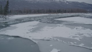 AK0001_1605 - 4K stock footage aerial video flying low over icy river toward snow covered shore, Knik River Valley, Alaska