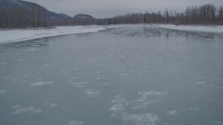 AK0001_1607 - 4K stock footage aerial video flying low over icy river toward snow covered shore, Knik River Valley, Alaska