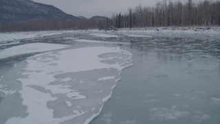 AK0001_1608 - 4K stock footage aerial video flying low over icy river toward snow covered shore, Knik River Valley, Alaska