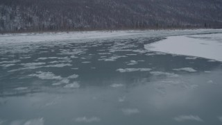 AK0001_1610 - 4K stock footage aerial video flying low over icy river toward snow covered shore, Knik River Valley, Alaska