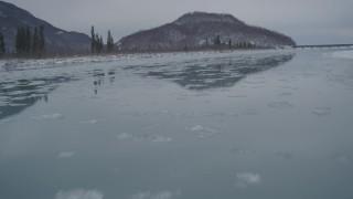 AK0001_1611 - 4K stock footage aerial video icy river, snowy shore, reveal Glenn Highway bridge, Knik River Valley, Alaska