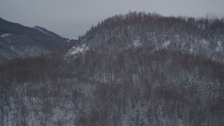 AK0001_1612 - 4K stock footage aerial video flying over snow covered, wooded hill revealing Glenn Highway, Anchorage, Alaska
