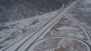 AK0001_1613 - 4K stock footage aerial video tilting up the length of snow covered Glenn Highway, Anchorage, Alaska