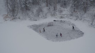AK0001_1629 - 4K stock footage aerial video kids playing ice hockey on iced over lake, Chugiak, Alaska in snow