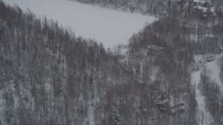 AK0001_1630 - 4K stock footage aerial video flying away from kids playing hockey, homes in snow covered woods, Chugiak, Alaska