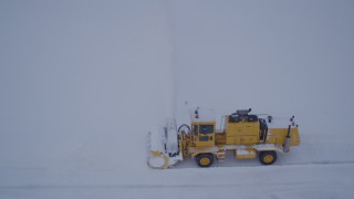 AK0001_1647 - 4K stock footage aerial video flying by a snow plow clearing Merrill Field at twilight, Anchorage, Alaska