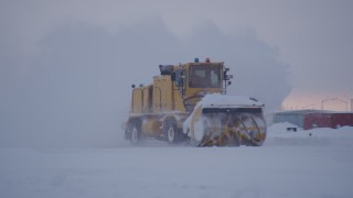 AK0001_1648 - 4K stock footage aerial video passing a snow plow clearing Merrill Field at twilight, Anchorage, Alaska