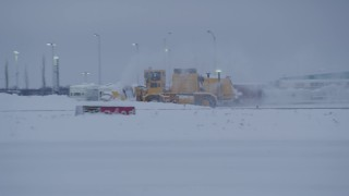 AK0001_1650 - 4K stock footage aerial video buildings at Merrill Field, reveal passing snow plow, Anchorage, Alaska, twilight