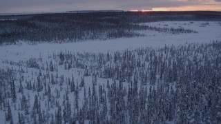 AK0001_1671 - 4K stock footage aerial video flying low over frozen, snowy ground at twilight on Point MacKenzie, Alaska